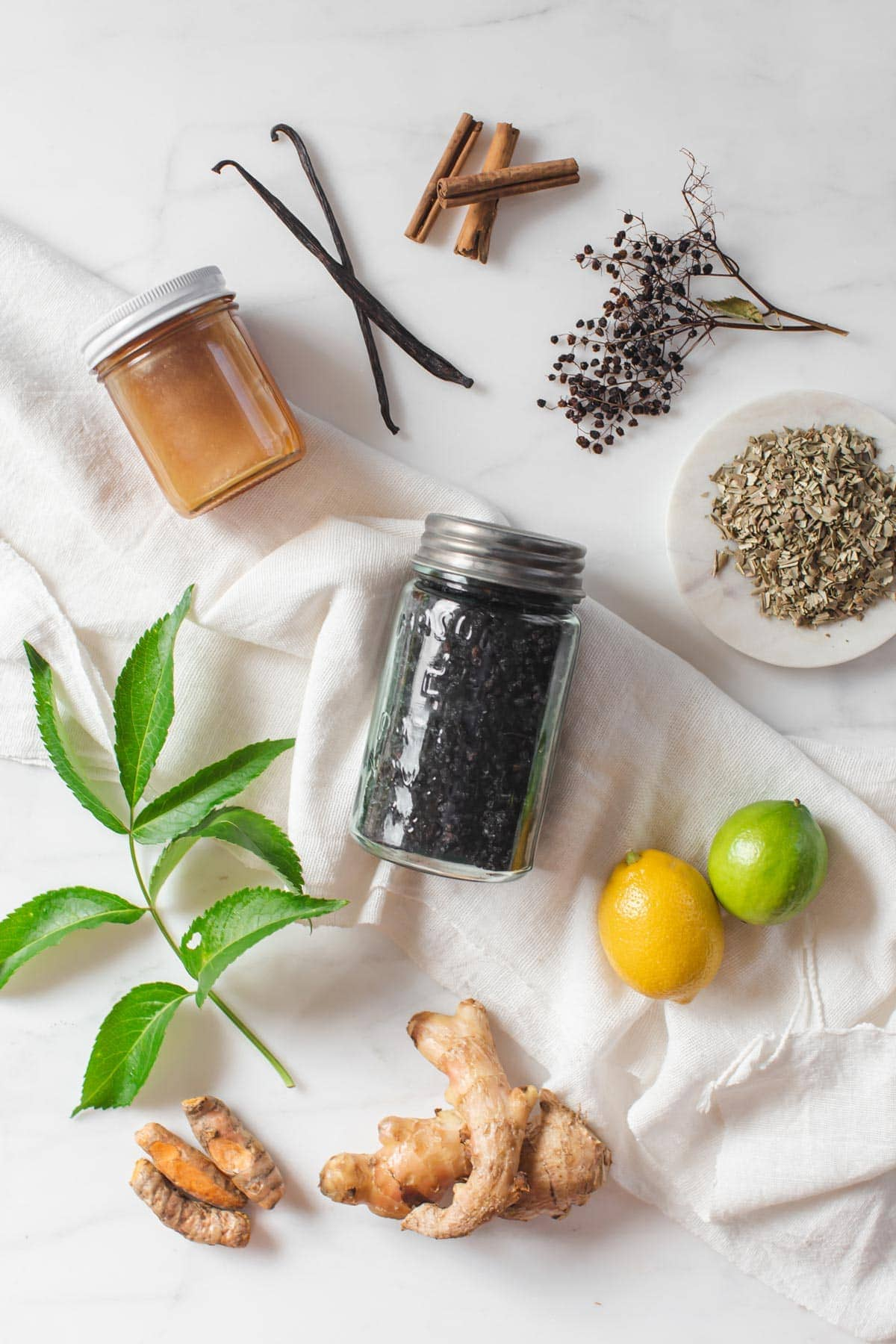 Flat lay of ingredients used to make a flavoursome herbal syrup - including dried elderberries, Manuka honey, spices and citrus fruits.
