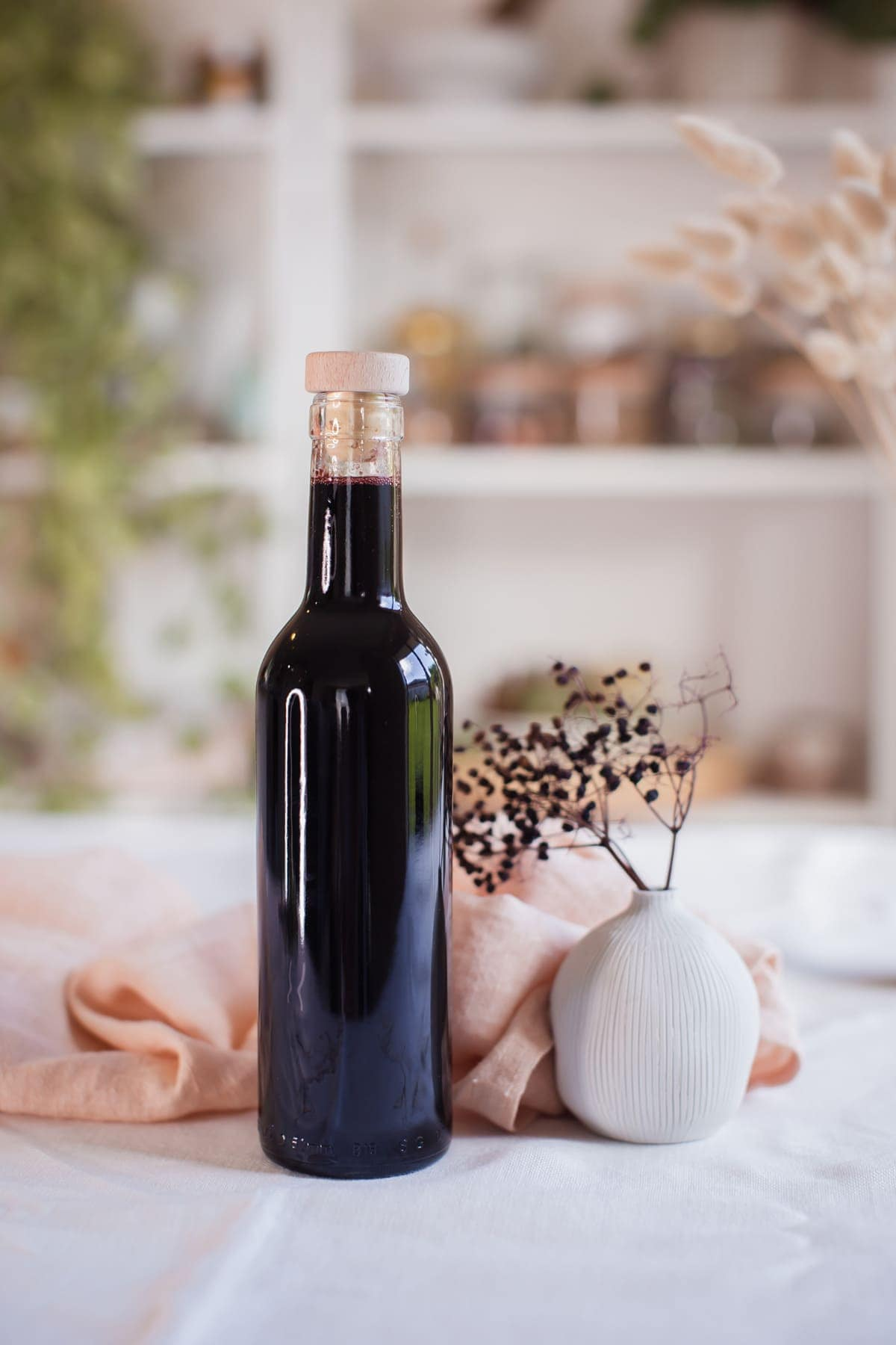 A 500ml glass bottle filled with deep purple elderberry syrup, on the kitchen table with a bookcase filled with dried herbs in glass jars in the background.