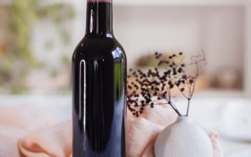Bottle of rich purple coloured elderberry syrup capped with a cork