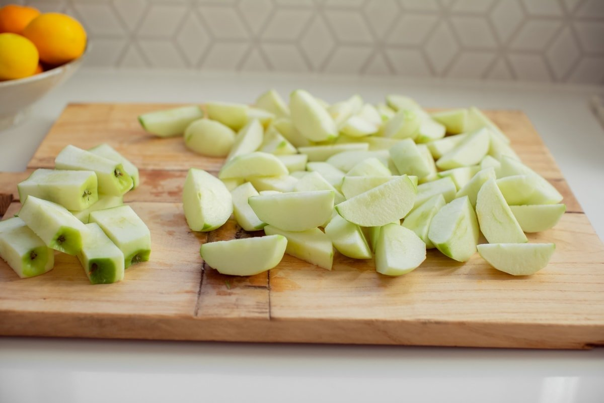 Peeled and cored apples cut into rough chunks ready to steam.