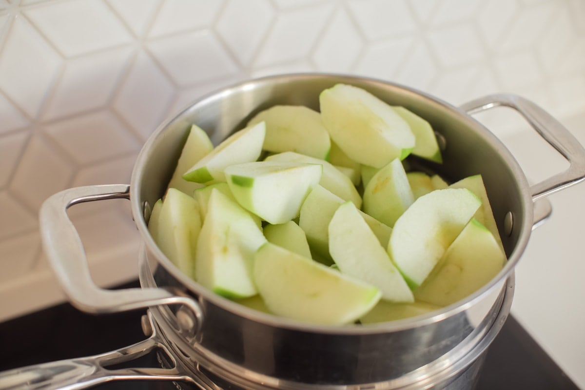 Overhead shot of a steamer over a saucepan, filled with chopped apples.