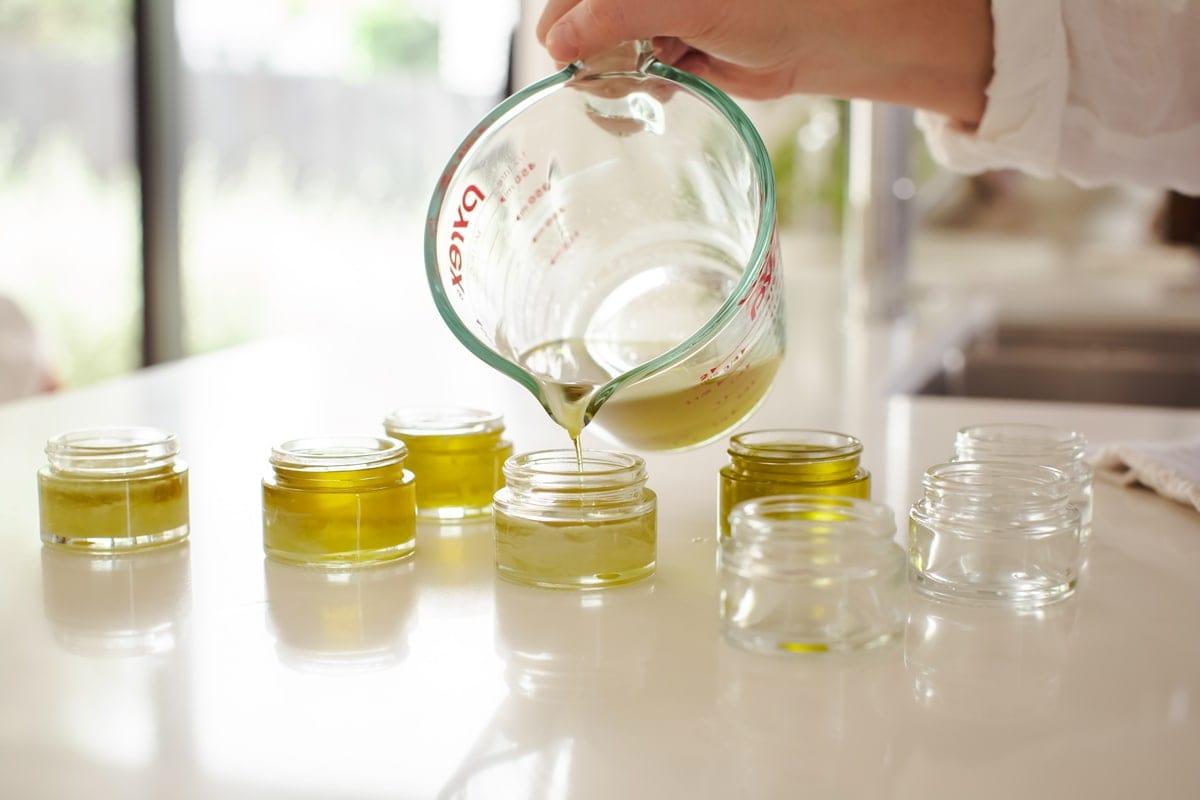 Lauren pouring the liquid salve into multiple small glass jars.