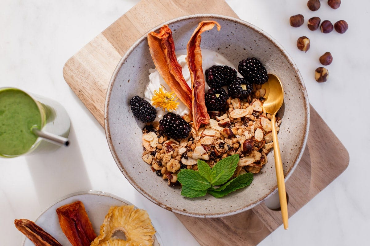 A ceramic bowl filled with crunchy granola, coconut yoghurt, blackberries and papaya.