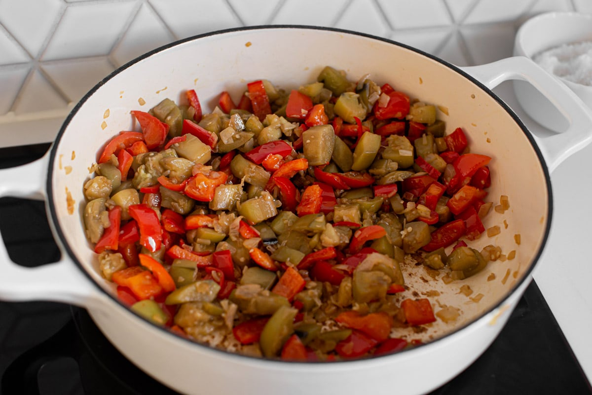Well cooked eggplant and bell peppers with a few other ingredients in a heavy-bottomed saucepan on the stove