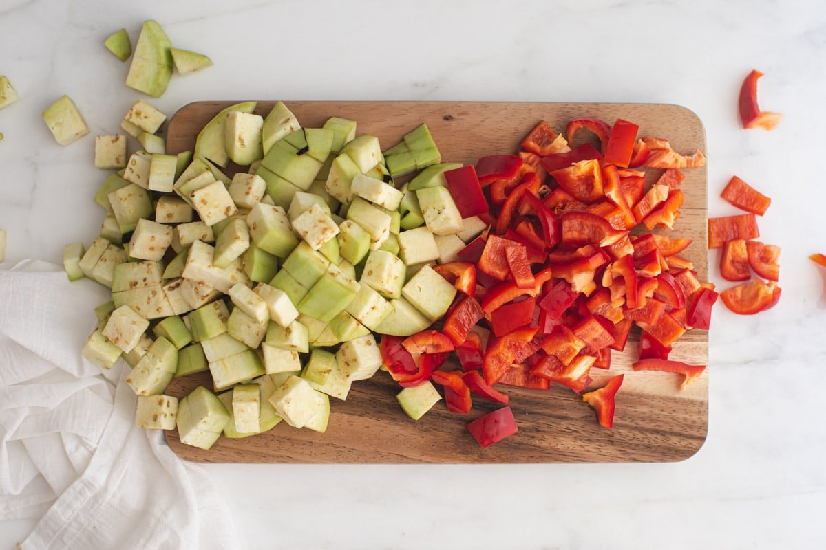 Wooden chopping board piled with cubed eggplant and sliced bell peppers