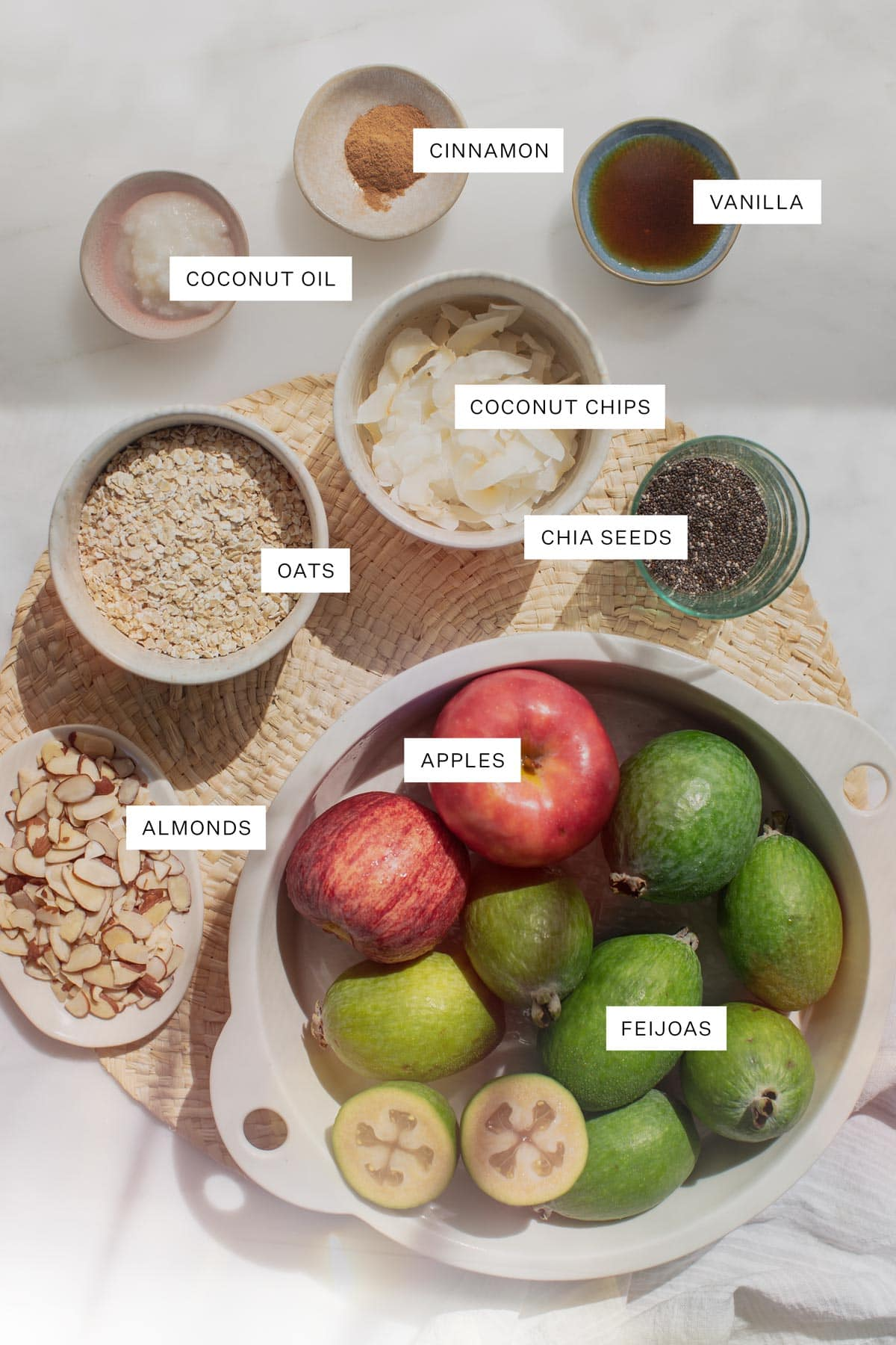 Flat lay of all the ingredients needed for this recipe - including feijoas, apples, oats, almonds, coconut flakes, cinnamon, chia, coconut oil, maple syrup