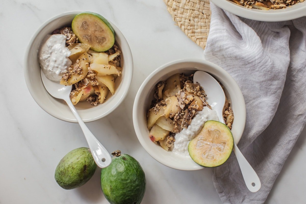 Two dessert bowls filled with hot crumble and a dollop of coconut yoghurt