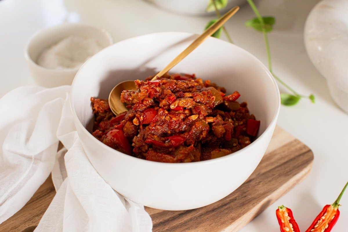 Bowl of cooked eggplant and bell pepper dip on a wooden serving board, with fresh chili in the background.
