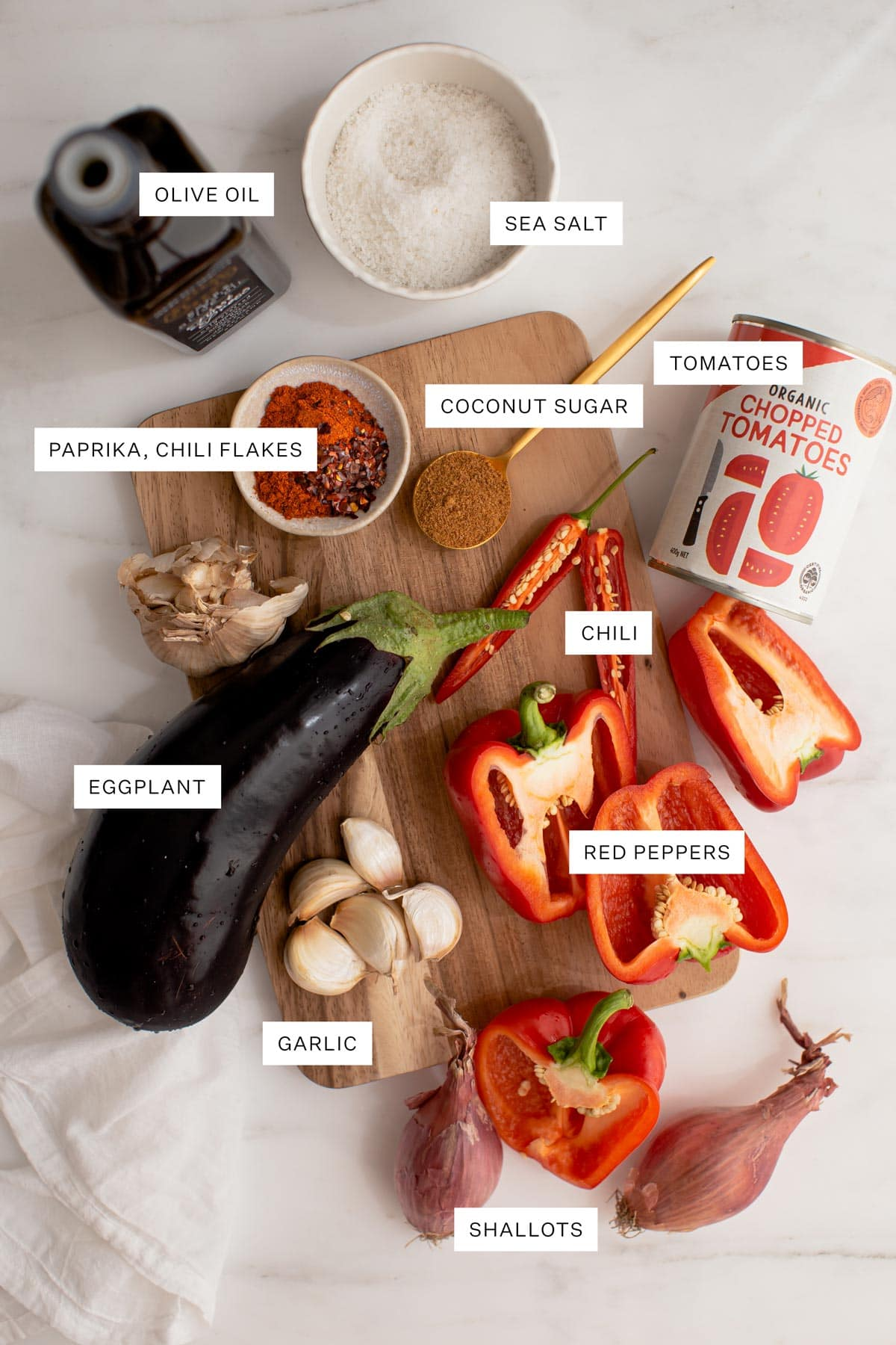 Flat lay of all the ingredients used to make this recipe - olive oil, salt, paprika, chili, coconut sugar, tinned tomatoes, eggplant, bell peppers and garlic.