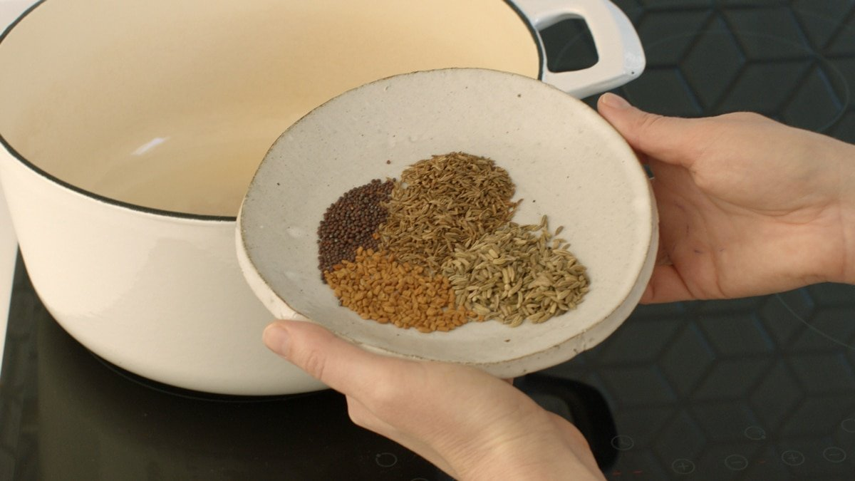 A dish filled with whole spices - mustard, fenugreek, fennel and cumin, about to go into the pot