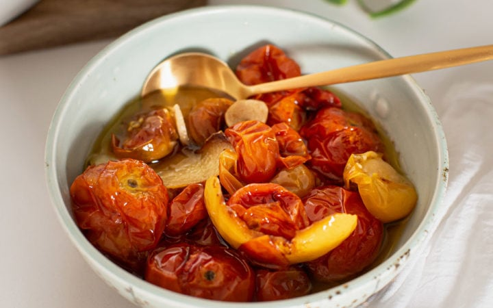 Ceramic bowl filled with juicy, blistered confit tomatoes
