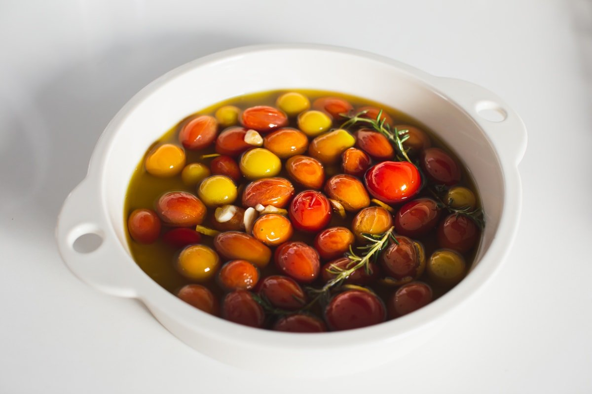 White baking dish with a single layer of tomatoes, covered in oil oil - it is now ready to go in the oven for several hours