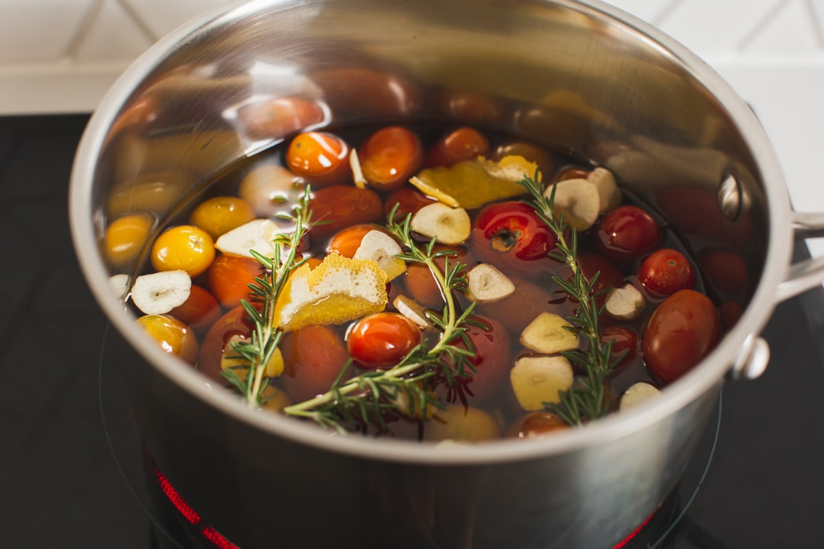 Saucepan on the element with tomatoes, herbs, garlic, lemon peel and honey - all submerged in olive oil. Tiny bubbles at the surface - it's warm but not boiling