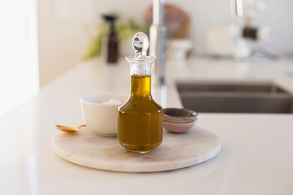 A glass bottle with a stopper filled with the remaining confit oil, on a marble platter beside other seasonings - salt, black pepper.